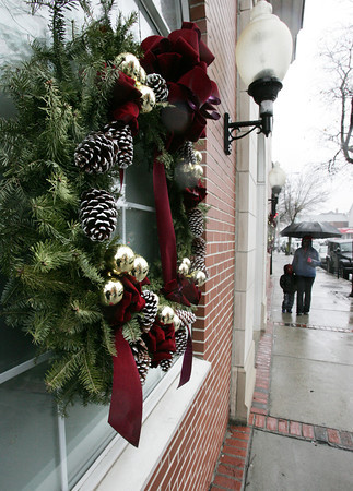 Beverly:<br /> Joy Sturrup and her son Dontae, who is wearing a Spiderman mask, walk in the rain near one of the  wreaths decorating Cabot Street in Beverly.<br /> Photo by Ken Yuszkus/The Salem News, Monday, December 17, 2012.