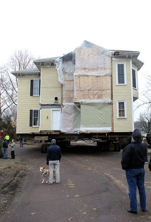A few spectators watch as a house on Pickman Road in Beverly is moved slowly down the street on Tuesday afternoon. David Le/Staff Photo