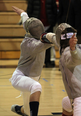 St. John's Prep fencer Will Collibe, left, exchanges blows with his Concord-Carlisle opponent on Thursday evening. David Le/Staff Photo