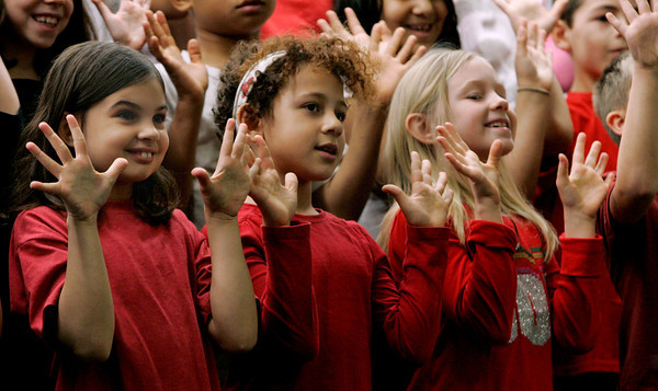 Salem:<br /> From left, Christiana Leahy, Eva Moreno, and Kaitlyn Colburn sing and gesture during the 3rd grade's chorus performance at the Bates School.<br /> Photo by Ken Yuszkus/The Salem News, Tuesday, December 4, 2012.