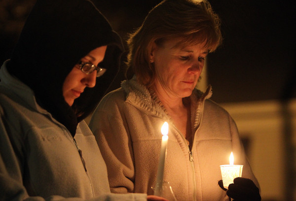Brenda and Katie Avigian, of Beverly, hold candles during a vigil at Beverly Common on Friday evening to remember the victims from the elementary school shooting in Connecticut. David Le/Staff Photo
