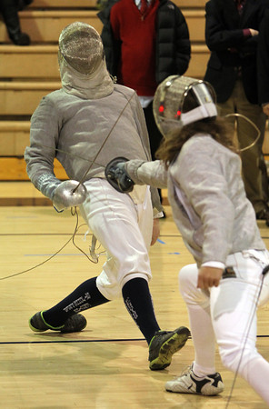 St. John's Prep fencer Ethan Smith, left, dodges out of the way of a stab from his Concord-Carlisle opponent on Thursday evening. David Le/Staff Photo