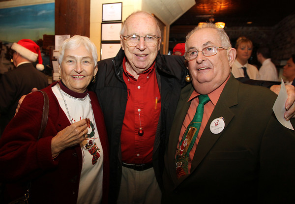 From left, Lois Nicholson, Joe Perkins, and John Walsh, at the Salem Children's Charity Christmas Party at Victoria's Station in Salem. David Le/Staff Photo