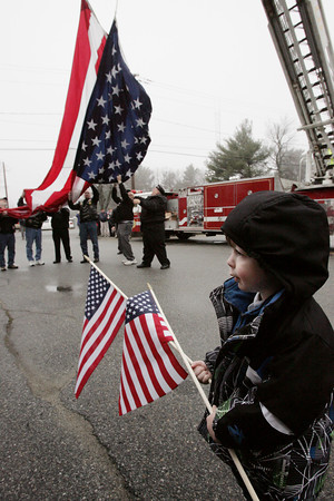 Topsfield:<br /> Tyler Moody, 3, of Danvers, holds two flags as he watches the flag being raised between two ladder firetrucks at the front gate of the Topsfield Fairgrounds before Wreaths Across America rolls into the Topsfield Fairgrounds. Wreaths Across America is a convoy taking wreaths from a farm in Maine to Arlington National Cemetery in Washington, DC for the annual wreath laying ceremonies on Saturday, December 15, 2012.<br /> Photo by Ken Yuszkus/The Salem News, Monday, December 10, 2012.