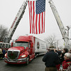 Topsfield:<br /> Wreaths Across America rolls into the front entrance of the Topsfield Fairgrounds under the large flag hung between two ladder firetrucks.  Wreaths Across America is a convoy taking wreaths from a farm in Maine to Arlington National Cemetery in Washington, DC for the annual wreath laying ceremonies on Saturday, December 15, 2012.<br /> Photo by Ken Yuszkus/The Salem News, Monday, December 10, 2012.
