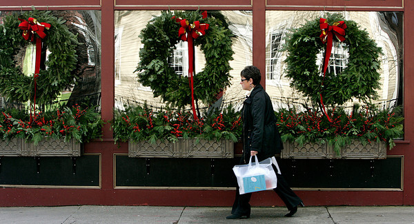 Salem:<br /> Alexandra MacAaron of Marblehead walks past wreaths decorating a store front while she was shopping for Christmas presents on Essex Street in Salem.<br /> Photo by Ken Yuszkus/The Salem News, Tuesday, December 11, 2012.
