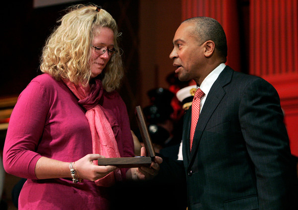 Worcester:<br /> Amy Rice, wife of Peabody firefighter James Rice who died fighting a fire in Peabody, views the medal of honor presented to her by Governor Deval Patrick on stage at Mechanic's Hall.<br /> Photo by Ken Yuszkus/The Salem News, Tuesday, December 18, 2012.