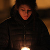 Sylvia Burger, 14, of Beverly, holds a candle and bows her head in remembrance for the victims of the elementary school shooting in Connecticut at Beverly Common on Friday evening. David Le/Staff Photo