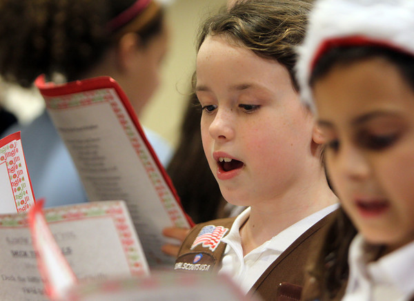 Brownie Scout Caitlin Estella, of St. John's Peabody sings Christmas Carols to residents gathered at the Towne Center at Brooksby Village on Wednesday afternoon. David Le/Staff Photo