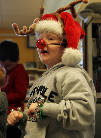 """Dylan Prime, 7, of Peabody, sings along to """"Jingle Bells"""" while sporting reindeer antlers and a flashing red nose at a Holiday Sing-a-long at Peabody Public Library on Saturday morning. David Le/Staff Photo"""