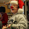 "Dylan Prime, 7, of Peabody, sings along to ""Jingle Bells"" while sporting reindeer antlers and a flashing red nose at a Holiday Sing-a-long at Peabody Public Library on Saturday morning. David Le/Staff Photo"