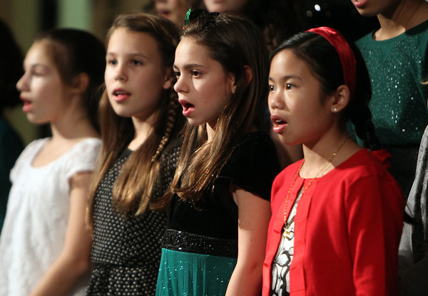 From left, Beverly Briscoe 6th graders Remy Normand, Natalie Stilwell, and Mary Galante, sing along with the 6th grade chorus to Holiday songs during the winter concert on Thursday evening. David Le/Staff Photo