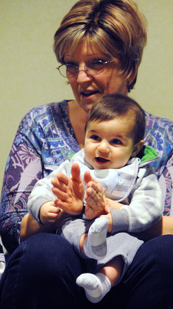 Beverly:<br /> Jeannette Lyons helps Fares Mowchantaf, 6 months old, clap and sing a song during the Toddler Story Time at the Beverly Public Library on Wednesday morning.<br /> Photo by Ken Yuszkus/The Salem News, Wednesday, February 20, 2013.