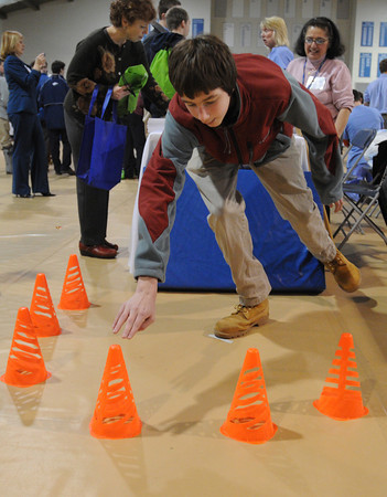"""Danvers:<br /> St. John's Prep freshman Aidan Crowley of Topsfield  tries the """"standing reach for balance"""" activity at the Lahey Clinic table during the first ever wellness fair for students at St. John's Prep. <br /> Photo by Ken Yuszkus/The Salem News, Thursday, February 28, 2013."""