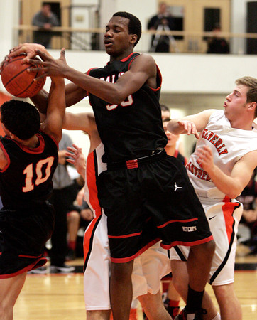 Beverly:<br /> Salem's Marvin Baez, left, and Salem's David Kazadi reach for the rebound together under Beverly's net as Beverly's Zach Duguid recoils during the Salem at Beverly boys basketball game.<br /> Photo by Ken Yuszkus/The Salem News, Friday, February 15, 2013.