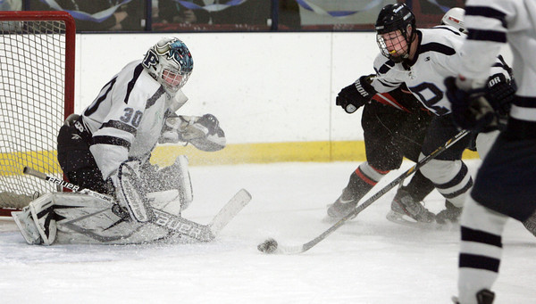 Peabody:<br /> Peabody's goalie Joe Powers watches the puck as his teammate Chris Minter tries to deflect a shot at the goal during the annual Carlin Cup hockey game with Beverly and Peabody.<br /> Photo by Ken Yuszkus/The Salem News, Monday, February 18, 2013.
