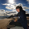 Beverly:<br /> Endicott College student Courtney Jennings makes a music selection to listen to while seated on the seawall in the sunshine at Dane Street Beach Monday afternoon.<br /> Photo by Ken Yuszkus/The Salem News, Monday, February 25, 2013.