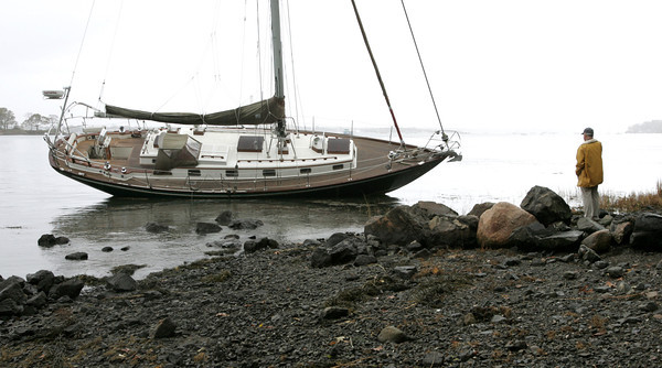Marblehead:<br /> A man calls his brother-in-law on Tuesday morning to tell him about the damage to the brother-in-law's sailboat which got loose during the storm in Salem Harbor and was beached.<br /> Photo by Ken Yuszkus/The Salem News, Tuesday, October 30, 2012