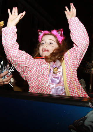 Giavanna Pasquerelli, 6, of Beverly, throws candy to crowds of people near Salem Common on Thursday evening during the annual Halloween Parade. David Le/Staff Photo