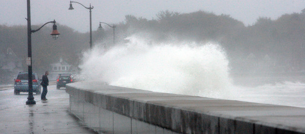 Marblehead:<br /> Richard Minney takes a close look at the waves crashing against the seawall of Ocean Avenue at Devereux Beach during high tide.<br /> Photo by Ken Yuszkus/The Salem News, Monday, October 29, 2012.