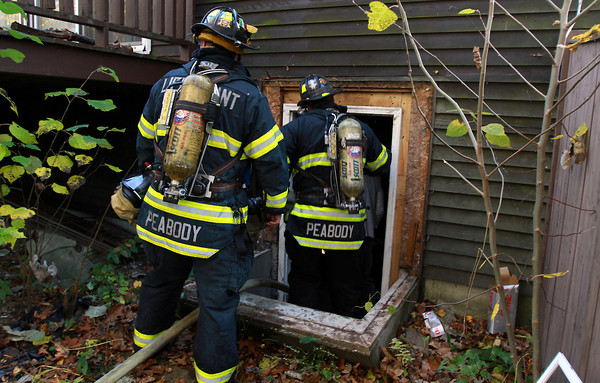 Peabody firefighters check out the basement of a Helen Road house which caught fire on Friday afternoon.  David Le/Staff Photo