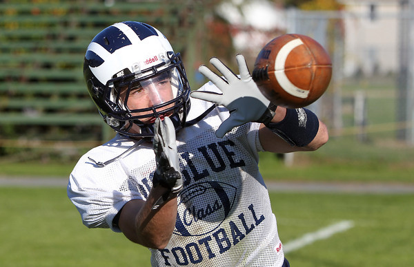 Swampscott senior receiver Robert Serino hauls in a pass from quarterback Brian Santry at practice on Thursday afternoon. The Big Blue will take on the Salem Witches at Blocksidge Field on Saturday afternoon. David Le/Staff Photo