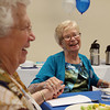 Barbara Noyes, a member of the Peabody High School Class of 1942, right, holds hands with Addy Emmett, at their 70th Class Reunion at the Torigian Community Life Center on Friday. David Le/Staff Photo