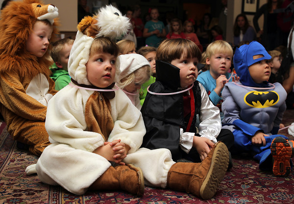 Reid Johnson, 4, left, and Samir Harb, 5, right, listen to storyteller Sharon Grimes at the Ipswich Museum on Friday afternoon. David Le/Staff Photo