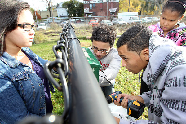 Salem Cyberspace students from left, Chanel Garcia, 15, Edwin Gonzalez, 14, Robert Abreu, 17, and Edili Tavarez, 15, work to install a Mutt Mitt, which provides disposible doggie bags for dog owners at Leslie's Retreat Dog Park in Salem. David Le/Staff Photo