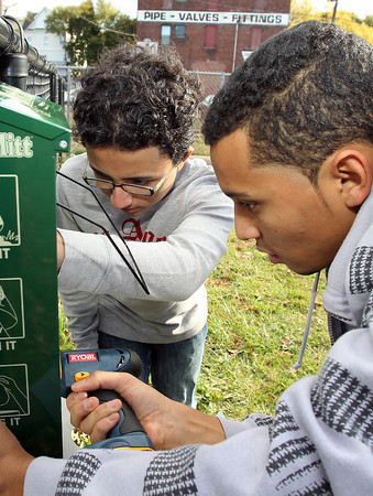 Edwin Gonzalez, 14, left, and Robert Abreu, 17, right, both of Salem Cyberspace, work to install a Mutt Mitt, disposible doggie bag despenser on Sunday afternoon. David Le/Staff Photo
