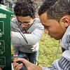 Edwin Gonzalez, 14, left, and Robert Abreu, 17, right, both of Salem Cyberspace, work to install a Mutt Mitt, disposible doggie bag despenser on Sunday afternoon. David Le/Staff Photo
