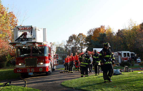 Peabody firefighters clean up the scene outside a house on Helen Road in Peabody on Friday afternoon. David Le/Staff Photo
