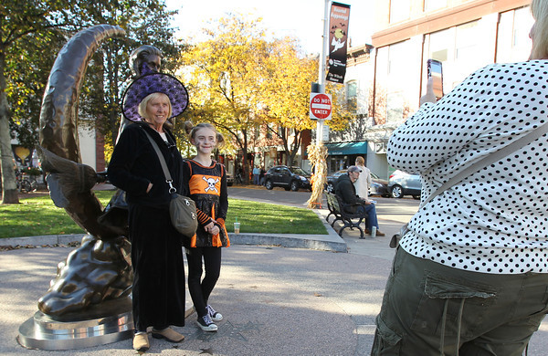 Lily Marshall, 9, and Sue Cunningham, left, of Gloucester, get their photo taken in front of the Bewitched Statue on Washington St. in Salem by Tracy Cunningham, right, on Thursday afternoon. In light of a possible hurricane next week, Salem anticipates thousands of people touring around the city this upcoming weekend. David Le/Staff Photo