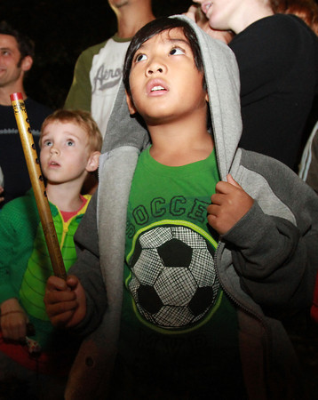Anton Baybay, 5, of Salem, watches as performers pass by and into Salem Common on Thursday evening. David Le/Staff Photo