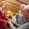 US Senate candidate Elizabeth Warren, left, chats and shakes hands with Brooksby Village resident Richard Thornburg, right, and Dot Brett, center, on Monday afternoon inside the Interfaith Chapel at Brooksby Village. David Le/Staff Photo