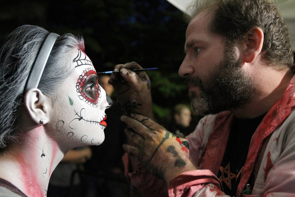Tania Rodrigues, left, of Trumbull, CT, gets her face painted by Marshall Tripoli, of Salem, right, in the Essex St. pedestrian mall on Saturday evening. David Le/Staff Photo