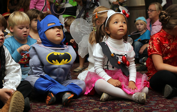 Twins Reed and Grace Wen, 4, listen to story teller Sharon Grimes at the Ipswich Museum on Friday afternoon.  David Le/Staff Photo