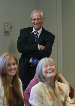 Marblehead resident Andrew Oliver, center, laughs while listening to speeches at a dedication in honor of Oliver and his wife Carla, right, on Tuesday afternoon. David Le/Staff Photo