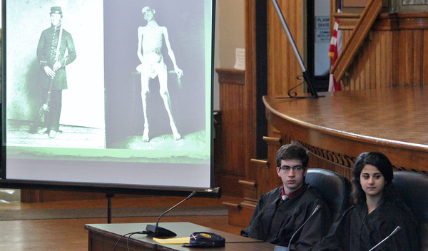 Alan Burke/Staff photo Graphic images of the suffering at Andersonville Prison during the Civil War are flashed on screen during the mock trial of Capt. Henry Wirz in Peabody. Judges Anthony Ferrara and Joanne Frangias follow the testimony.