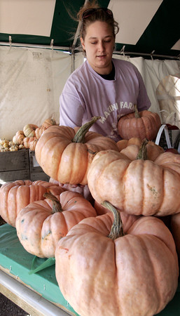 Ipswich:<br /> Samantha Levesque, employee at the Marini Farm, moves pink pumpkins on display. Marini Farm grew a special variety of pink pumpkin this year, with all proceeds from sales going to charity.<br /> Photo by Ken Yuszkus/The Salem News, Monday, October 22, 2012.