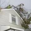 Salem:<br /> Alex Lopes is cutting the fallen limbs of a tree that landed on the house at 461 Loring Avenue in Salem. The tree limbs poked two holes in the roof.<br /> Photo by Ken Yuszkus/The Salem News, Monday, October 29, 2012.
