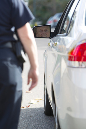 Danvers resident Gloria Lipinski, right, peers into her drivers side rear view mirror as Danvers Police Officer Suzanne Tibbetts performs a blind spot test. The Danvers Senior Center and Police Department are running a program called 'CarFit,' designed to instruct seniors on safe driving techniques. David Le/Staff Photo