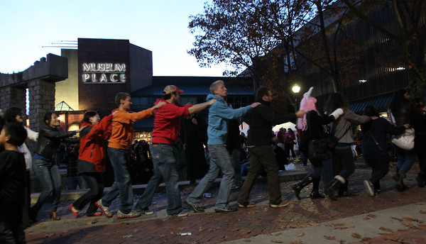 Halloween-goers near the Museum Place Mall form a congo line as they dance along with live music being played on Saturday evening. <br /> David Le/Staff photo
