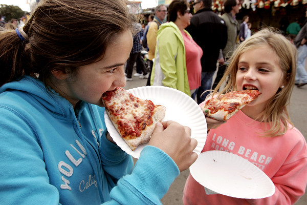 Topsfield:<br /> Bella Pomeroy, left, and her friend Suzy Morton, both of Manchester, bite into slices of pizza at the Topsfield Fair.<br /> Photo by Ken Yuszkus/The Salem News, Monday, October 8, 2012.