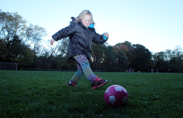 Tessa Manderson, 6, of Bevelry kicks a soccer ball around at the Cross Street soccer fields on Tuesday evening. David Le/Staff Photo