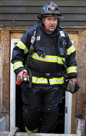 Peabody firefighter David Ahearn emerges from the basement of a Helen Road home after putting out a fire on Friday afternoon.  David Le/Staff Photo