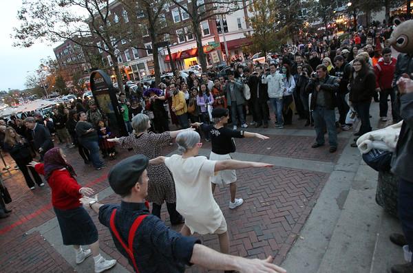 A large crowd gathers to watch flash mob dancers near Rockafellas on Washington St. in Salem on Saturday afternoon.  David Le/Staff Photo