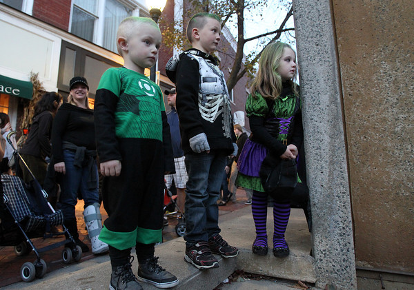 From left, Jameson Ryan, 3, JJ Stien, 7, and Kaleigh Ryan, 6, watch a small flash mob dancing near Rockafellas on Saturday afternoon.<br /> David Le/Staff photo