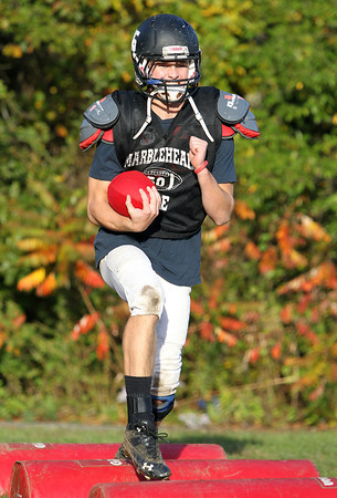 Marblehead running back Zac Cuzner high steps over pads during a drill at practice on Wednesday afternoon. Cuzner and the Magicians are gearing up for Gloucester on Friday evening. David Le/Staff Photo