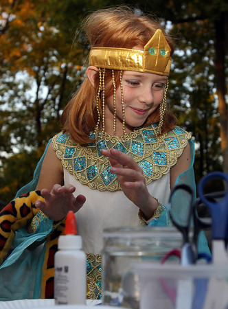 Erica Prisby, 9, of Ipswich, smiles as she decorates a Halloween ornament on Friday afternoon at the Ipswich Museum.  David Le/Staff Photo